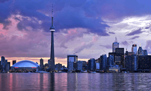 Toronto skyline against a colorful clouds at sunset.