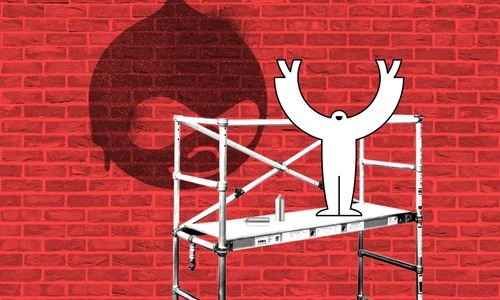 A yeti standing on scaffolding in front of a brick wall with the Drupal logo spray painted on it.