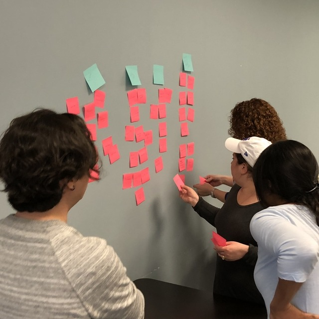 A second group of people putting stickies on the wall