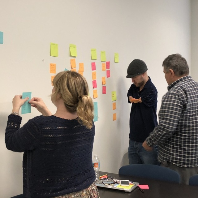 Group of people putting stickies on the wall