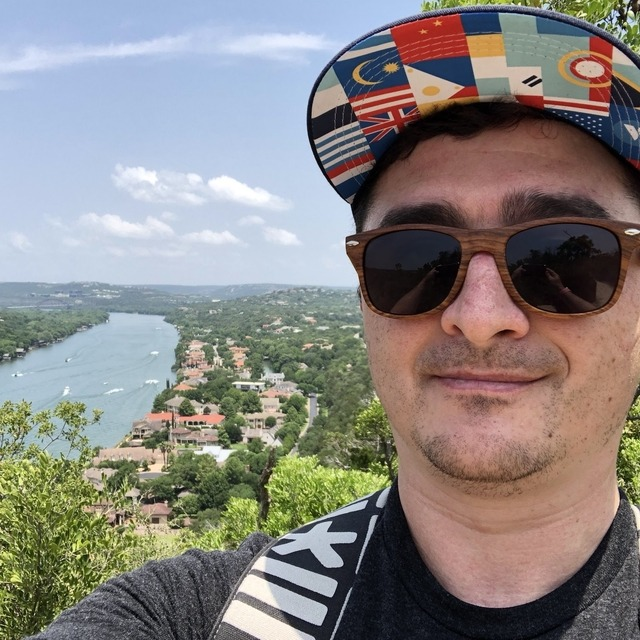 Kelly wearing a hat takes a selfie at Mt. Bonnell with the river behind him