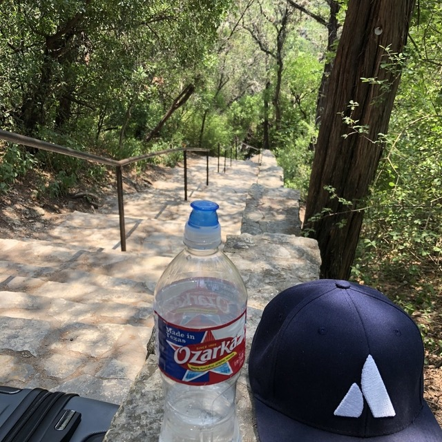 A water bottle and an Atlassian cap on a table