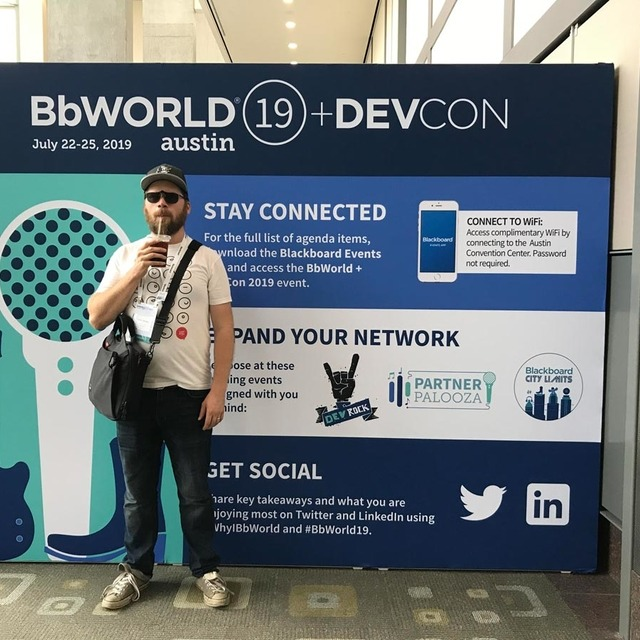 Colin Panetta drinking iced coffee standing in front of a banner with information about BBWorld.