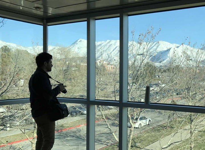 A photographer stands silhouetted against large windows through which can be seen the snow-capped mountains surrounding Utah.